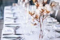 25 a stylish and cozy winter wedding table setting done in white and with cotton on branches for centerpieces is chic and cool