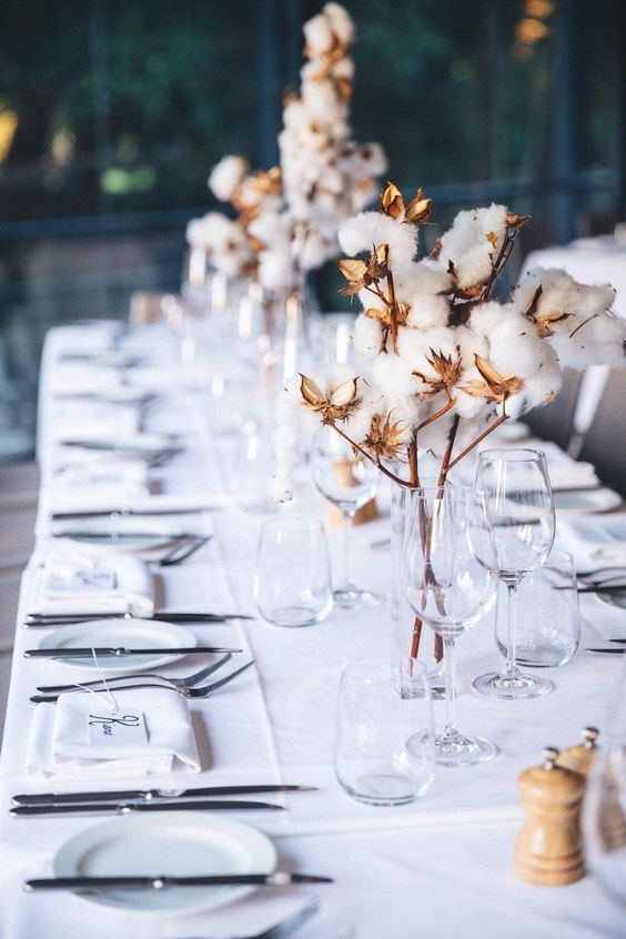 a stylish and cozy winter wedding table setting done in white and with cotton on branches for centerpieces is chic and cool