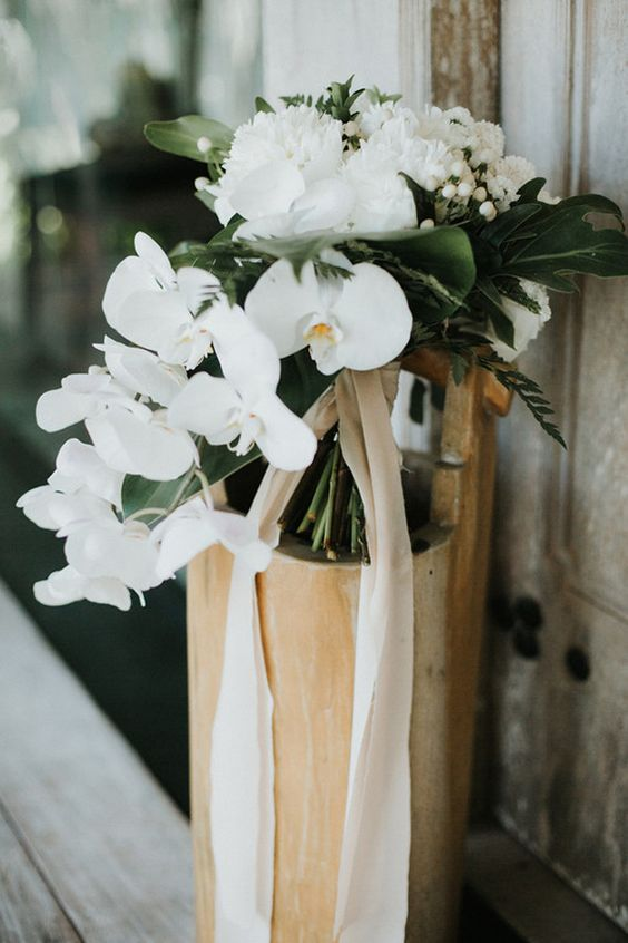 an elegant white wedding bouquet of cascading orchids, peonies, berries and foliage is a gorgeou sidea for a minimalist bride
