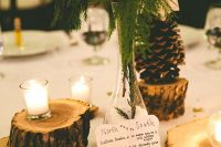 26 a rustic winter wedding centerpiece of tree stumps, candles, a pinecone, some cotton and evergreens is a simple to DIY arrangement