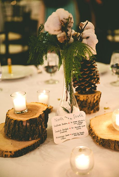 a rustic winter wedding centerpiece of tree stumps, candles, a pinecone, some cotton and evergreens is a simple to DIY arrangement