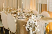 26 a sophisticated warm-colored winter wedding tablescape with a tan table runner, tan glasses, a cotton garland and an overhead decoration, tall candles