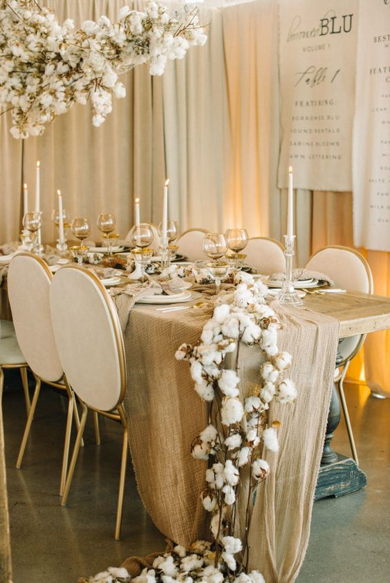 a sophisticated warm colored winter wedding tablescape with a tan table runner, tan glasses, a cotton garland and an overhead decoration, tall candles