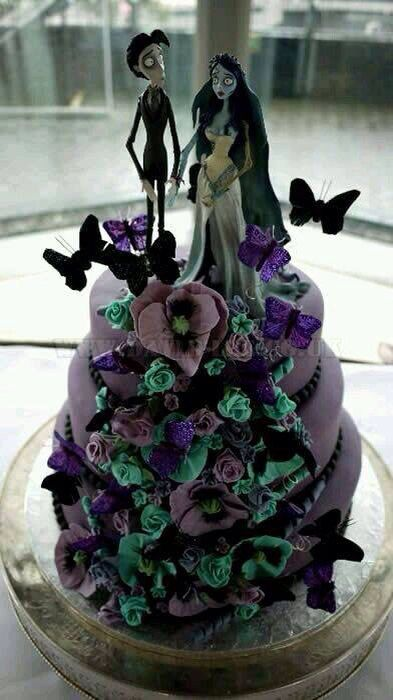 a statement lilac wedding cake with green, purple and lilac blooms, black butterflies and Jack and Sally cake toppers