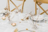 27 a refined white winter wedding tablescape with grey plates, gold touches, dried blooms, white linens is very stylish