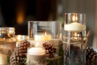 27 a rustic winter wedding centerpiece of greenery, floating candles in glasses wrapped with burlap and pinecones around is a cool and cute idea to rock