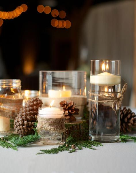 a rustic winter wedding centerpiece of greenery, floating candles in glasses wrapped with burlap and pinecones around is a cool and cute idea to rock
