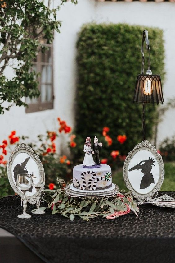 a Tim Burton wedding cake with themed cake toppers and small themed artworks plus greenery and blooms are adorable