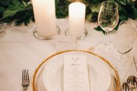 28 a refined neutral winter wedding tablescape with a greenery garland, a sheer and gold charger, pillar candles and refined silver cutlery