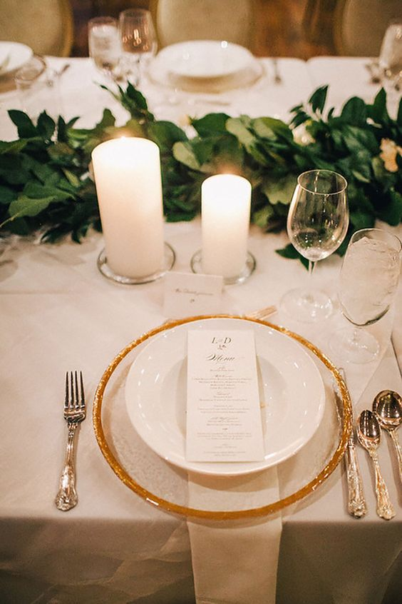 a refined neutral winter wedding tablescape with a greenery garland, a sheer and gold charger, pillar candles and refined silver cutlery