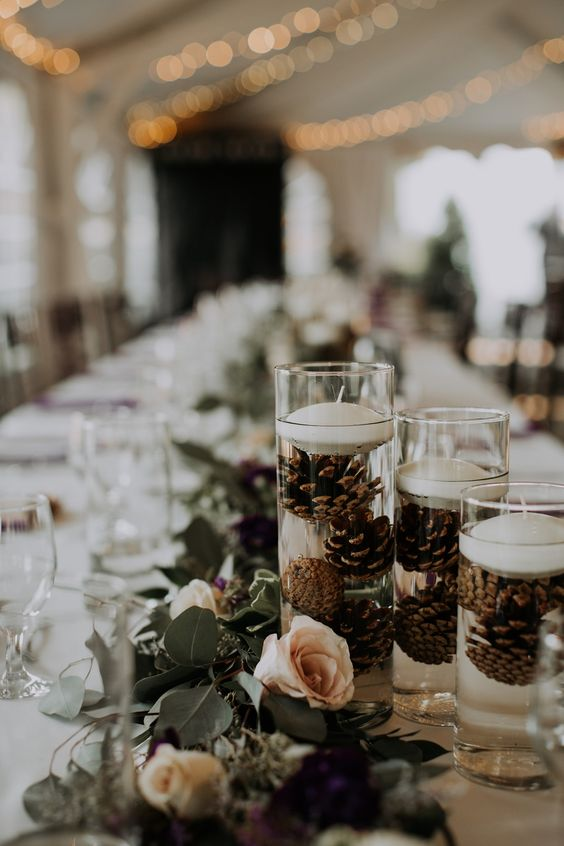 a greenery, blush rose wedding table runner, tall glasses with pinecones and floating candles for beautiful and a bit wild wedding decor
