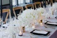 29 a refined all-white winter wedding tablescape with lush blooms and accented with black candles and napkins is awesome