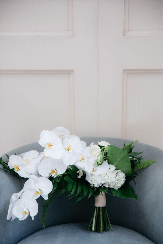 a textural and chic minimalist wedding bouquet of white orchids, hydrangeas and various foliage is a lovely idea to go for