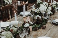 30 a beautiful winter wedding tablescape of greenery, white blooms, pinecones and tall and thin candles is a lovely idea for a winter woodland wedding