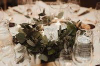 30 a pretty and chic winter wedding tablescape in neutrals, with candles, a greenery wreath, a wooden board and some black cards