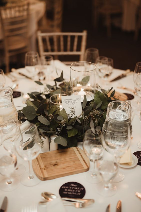 a pretty and chic winter wedding tablescape in neutrals, with candles, a greenery wreath, a wooden board and some black cards