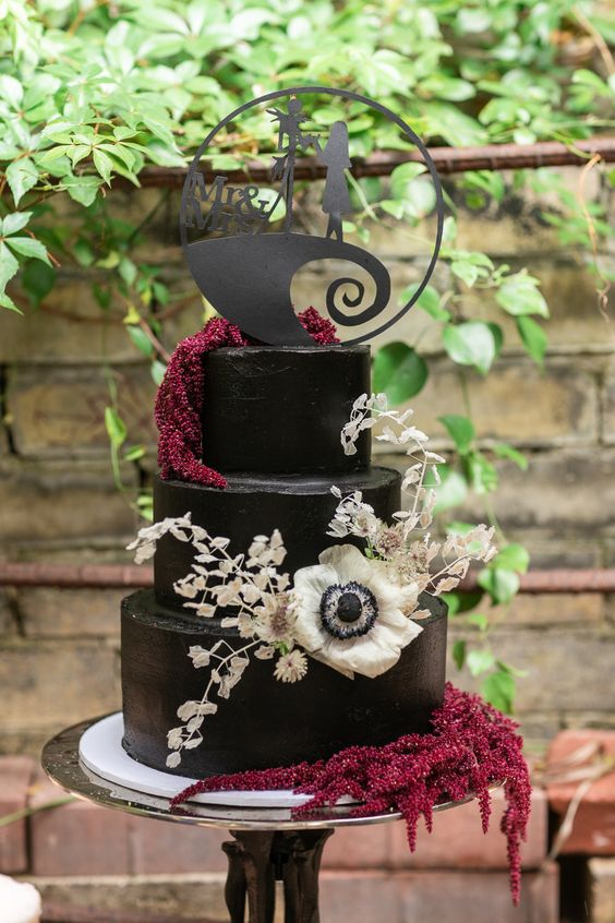 an elegant and chic Tim Burton wedding cake in black, with dried blooms and leaves and a lovely themed cake topper is amazing