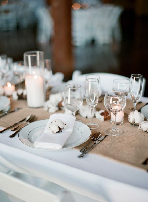 a neutral winter wedding tablescape with a burlap runner, cotton buds, pillar candles, white linens is cozy