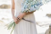 31 a romantic coastal bridal look with a strapless embellished wedding dress and a white and blue long stemmed wedding bouquet