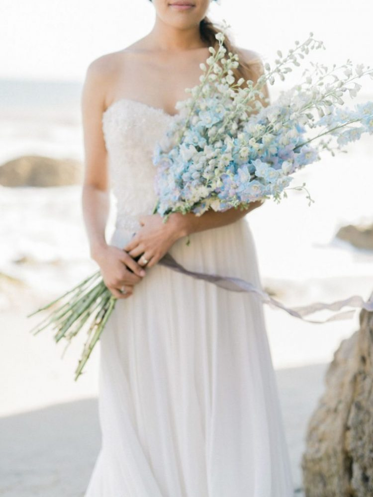 a romantic coastal bridal look with a strapless embellished wedding dress and a white and blue long stemmed wedding bouquet