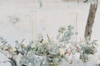 32 a neutral winter wedding tablescape styled with pale greenery and white blooms and the same over the table, neutral plates and menus