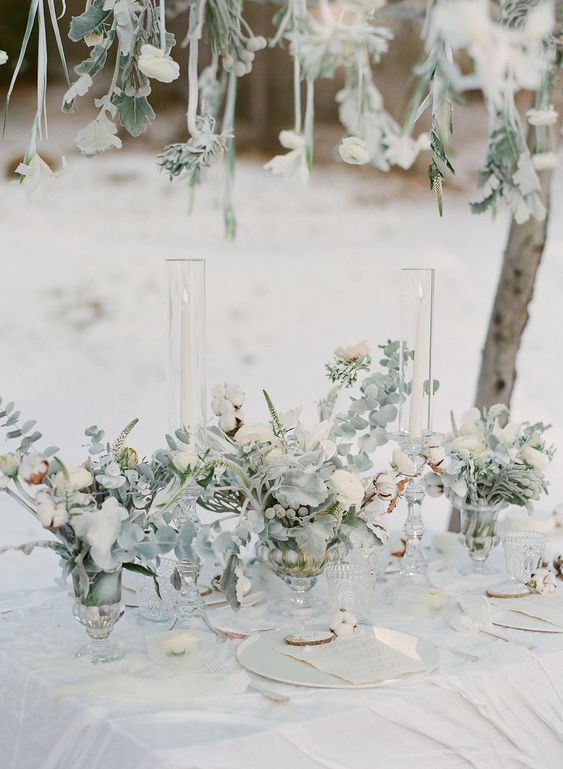a neutral winter wedding tablescape styled with pale greenery and white blooms and the same over the table, neutral plates and menus