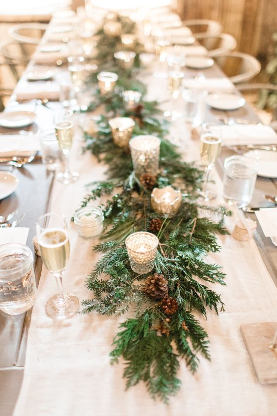 a winter wedding table runner of evergreens, pinecones and shiny candleholders with candles is a lovely idea for any type of winter wedding