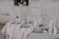 33 a neutral winter wedding table setting with textural linens, pillar candles, lunaria centerpieces and simple white porcelain