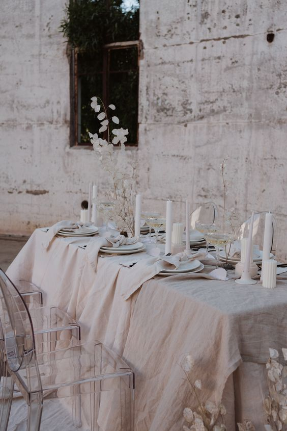 a neutral winter wedding table setting with textural linens, pillar candles, lunaria centerpieces and simple white porcelain