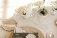 34 a neutral winter wedding place setting with white and blush roses and baby's breath, neutral plates and simple modern cutlery