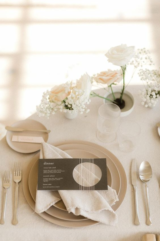 a neutral winter wedding place setting with white and blush roses and baby's breath, neutral plates and simple modern cutlery