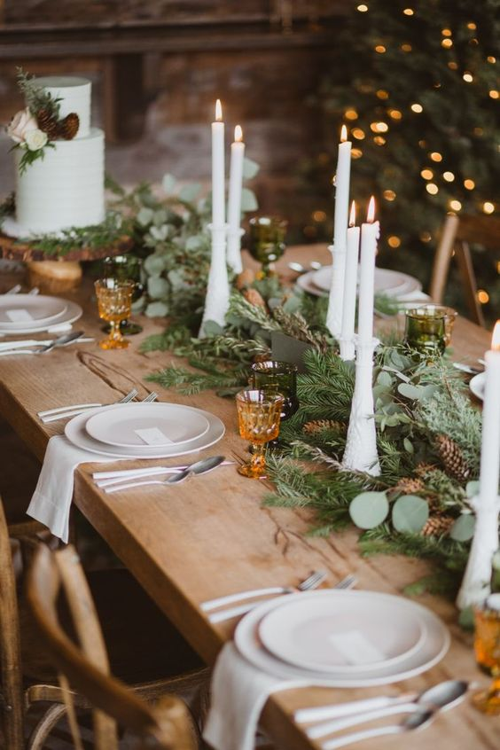 an evergreen and greenery table runner dotted with pinecones and with tall and thin candles is a beautiful and cozy idea for a winter wedding
