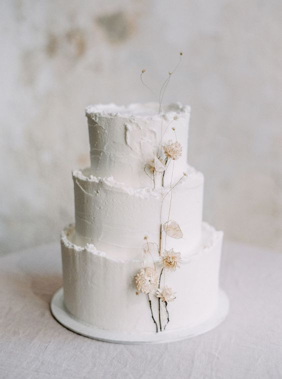 a textural white winter wedding cake with a raw edge and dried blooms is a lovely and cool idea that you may rock