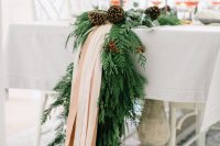 36 an exquisite winter table runner of evergreens, pinecones and blush ribbons will fit even the most refined winter wedding and will give ti a cozy feel