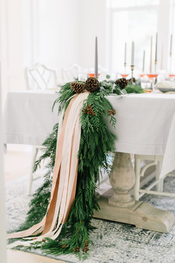 an exquisite winter table runner of evergreens, pinecones and blush ribbons will fit even the most refined winter wedding and will give ti a cozy feel