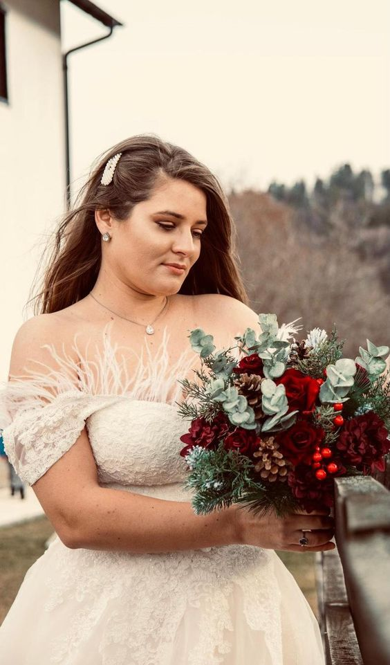 a Christmas wedding bouquet of red roses, berries, eucalyptus and pinecones is a gorgeous idea with plenty of color