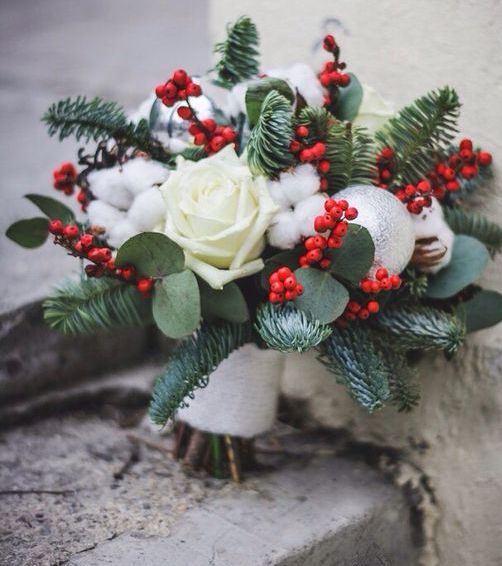 a Christmas wedding bouquet with holly berries, cotton, white roses and evergreens plus an ornament is a lovely and fresh solution