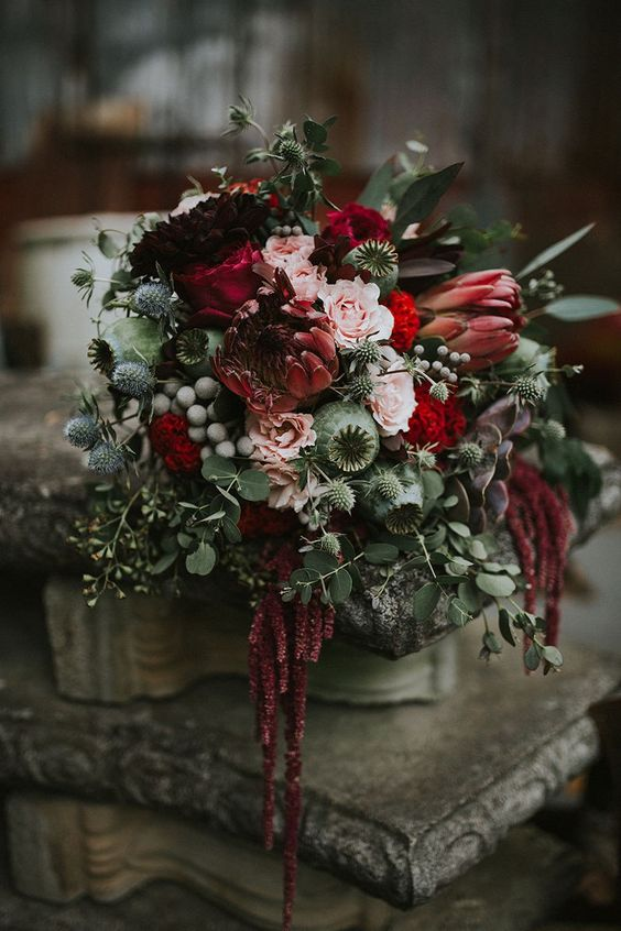 a Halloween wedding bouquet of pink and deep red blooms, thistles, seed pods, greenery, berries and cascading touches is amazing