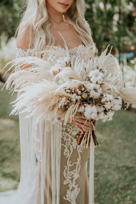 a beachy boho wedding bouquet of king proteas, cotton and pampas grass, with a burlap wrap is a lovely idea for summer or fall