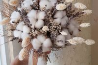a beautiful dried flower wedding bouquet of cotton, bunny tails, lavender and waxflower plus ribbons is a very cool and fresh idea