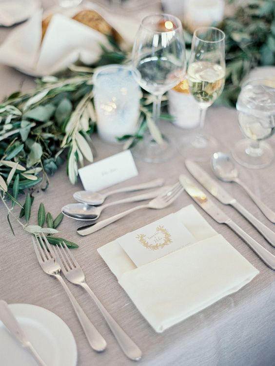 a beautiful greige wedding table setting with a greige tablecloth, white linens and cards, a greenery garland and pillar candles is chic