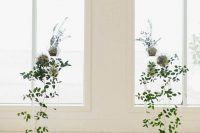 a beautiful minimalist wedding altar of acrylic stands with cascading greenery and some potted plants is an ethereal and serene idea for a spring wedding
