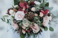 a beautiful pink wedding bouquet of blush and burgundy blooms, greenery, thistles, pinecones is a beautiful idea for both a fall or winter wedding