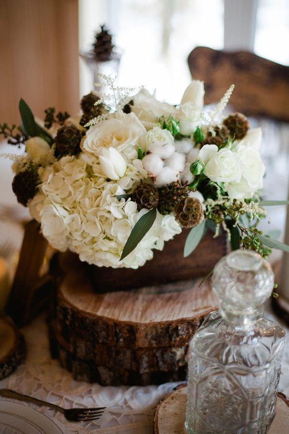 a beautiful rustic wedding centerpiece of wood slices, a wooden box with white roses, hydrangeas, seed pods, cotton and greenery