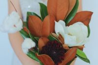 a beautiful southern wedding bouquet of magnolia leaves, magnolias, dahlias and cotton is a very out of the box idea that you may try