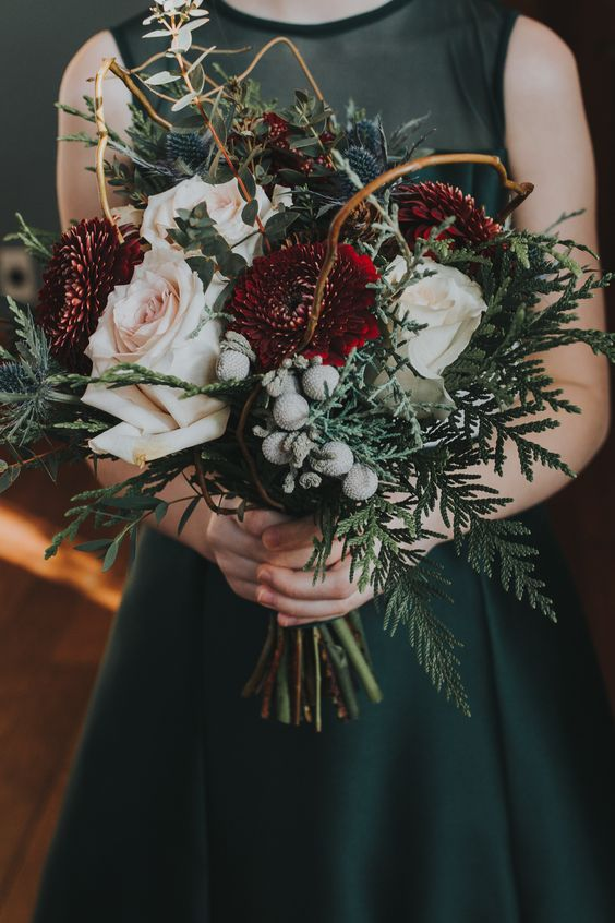 a beautiful winter wedding bouquet of white, blush and burgundy blooms, greenery, twigs, thistles and berries is a moody and chic idea to try