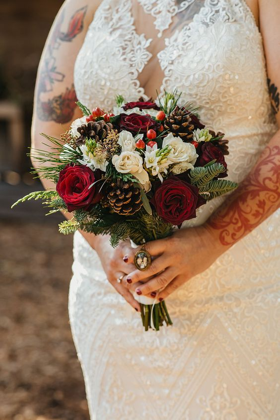 a bold Christmas wedding bouquet of red and white roses, berries, pinecones, evergreens and greenery is a classic idea of a bouquet