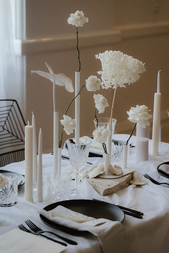a bold and edgy minimalist wedding tablescape with neutral linens, black chargers and cutlery, neutral candles of various sizes and white blooms