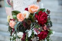 a bold fall wedding bouquet of peachy, white and hot red blooms, berries, greenery and pinecones is amazing for the fall