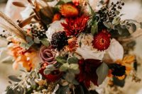 a bold fall wedding bouquet that includes burgundy, deep red, dusty pink, white and yellow blooms, greenery, grasses and privet berries